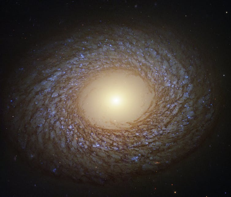 Computer enhanced image of a swirling galaxy with bright light at centre.