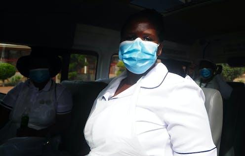 Una trabajadora de Suráfrica sanitaria con uniforme blanco y mascarilla sentada en un autobús