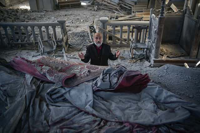 A man with grey beard prays in a church filled with debris