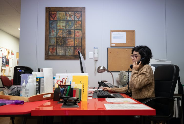 A woman on the phone sits at a desk in an office setting.