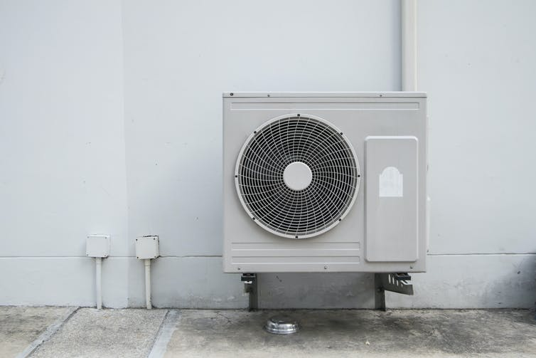 A large air compressor unit with fan is attached to a house with cables.