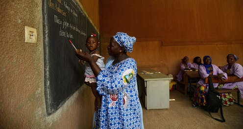 A woman holds a baby in front of a blackboard.