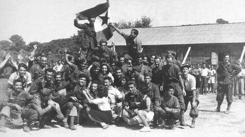 Soldiers posing for a photo during the liberation of a concentration camp.