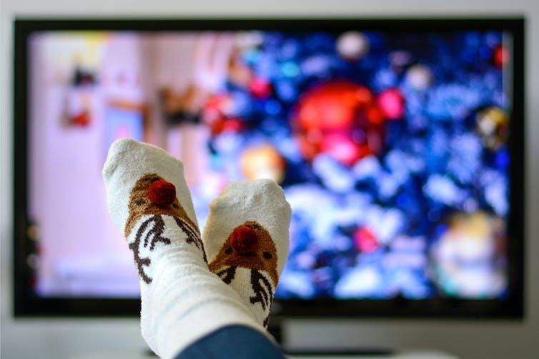 Feet in reindeer socks in front of a TV.