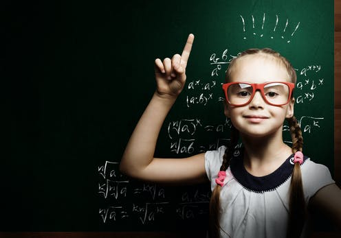 Young girl pointing up in front of blackboard.