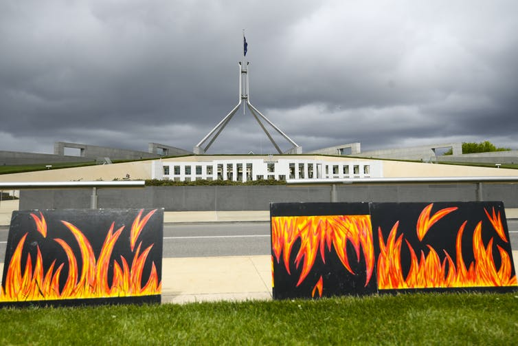 Posters depicting bushfire flames in front of Parliament House, Canberra