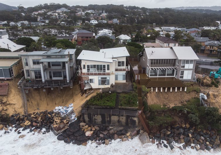 Houses damaged by storms along a beach