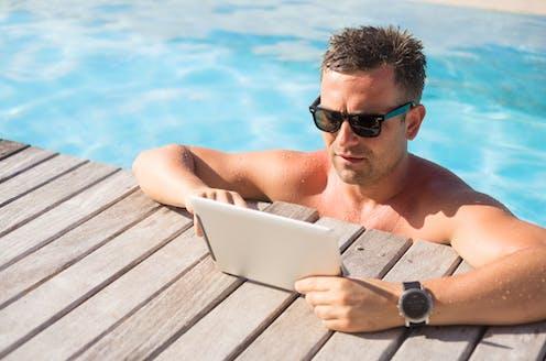 Man wearing sunglasses in swimming pool staring at iPad