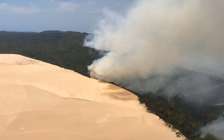 Smoke over bushland, beside sand