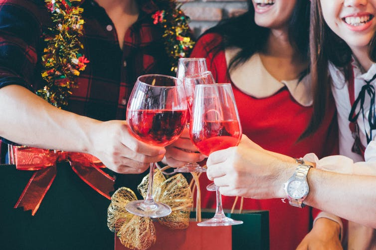 A group of friends clink drinks while wearing Christmas gear.