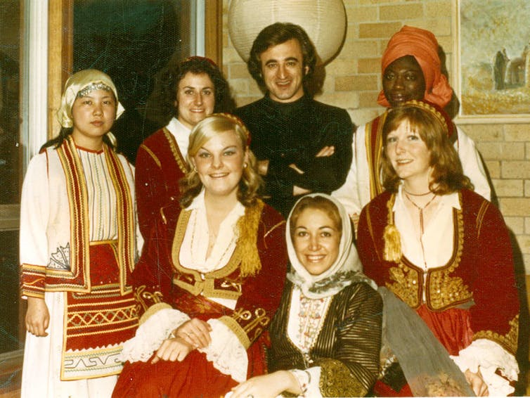 An international group of people dressed in traditional Greek costumes.