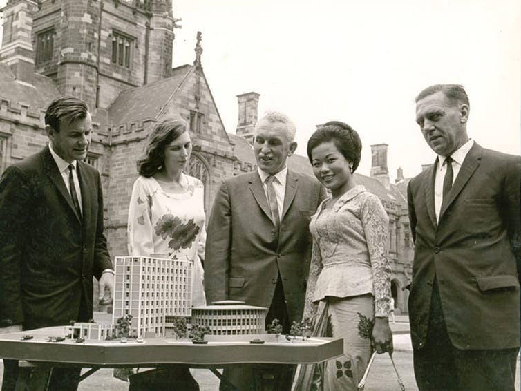 Harold Maze and four other people looking at a model of a building.