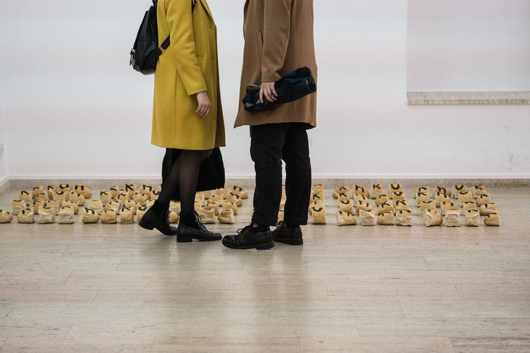 Two people look at small sculptures.