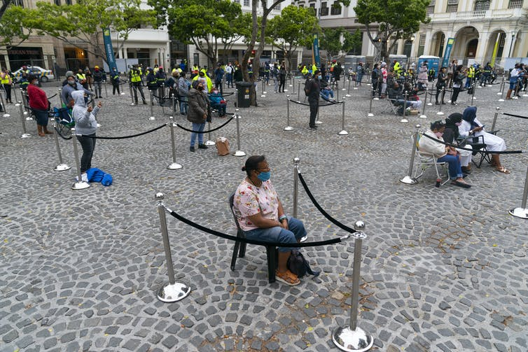 In a village square, people sit wearing masks at a distance from one another, their seating area marketed by ropes.