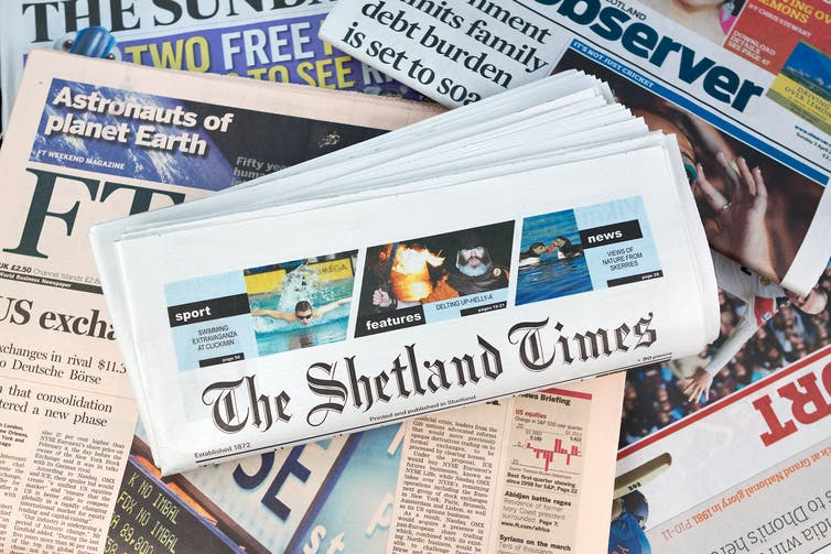 Shetland Times newspaper sits on a pile of UK national papers.