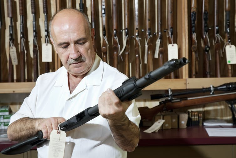 A man cocks a rifle, standing in front of a rack of rifles in a US gun shop.