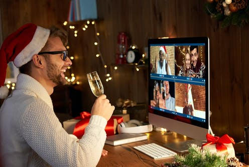Man in Santa hat with champagne on video call with friends