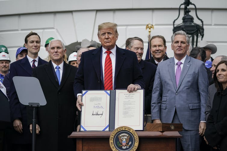 Trump stands with a document in front of him, surrounded by people including Vice President Mike Pense and son-in-law Jared Kushner