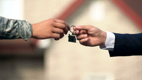 Person in suit handing person in army uniform key to house