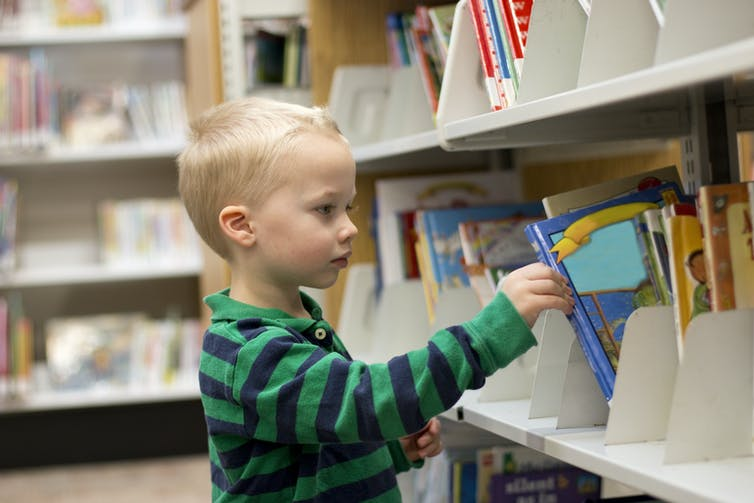 Little boy picking a book off a library shelf