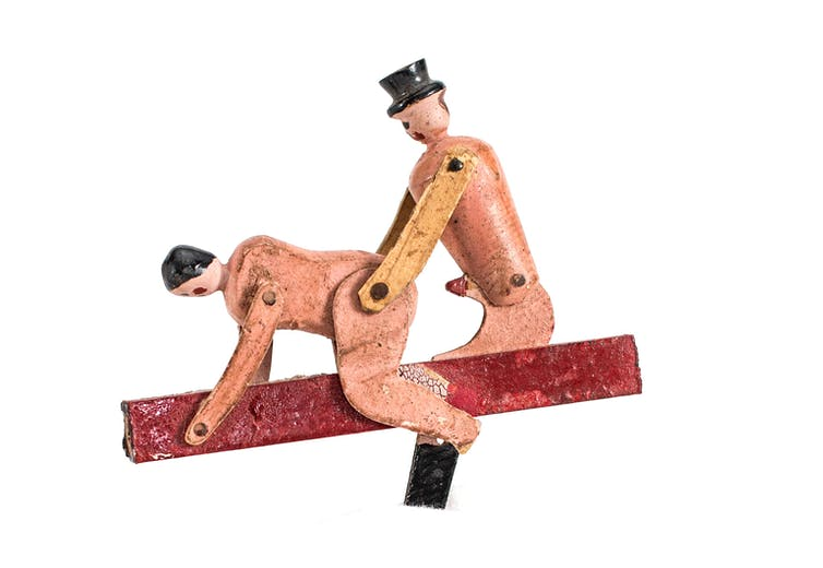 Naked wooden figures in a sexual postiion.