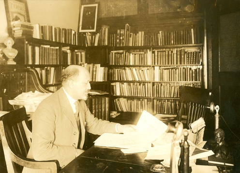 W.E.B. Du Bois seated at desk in office