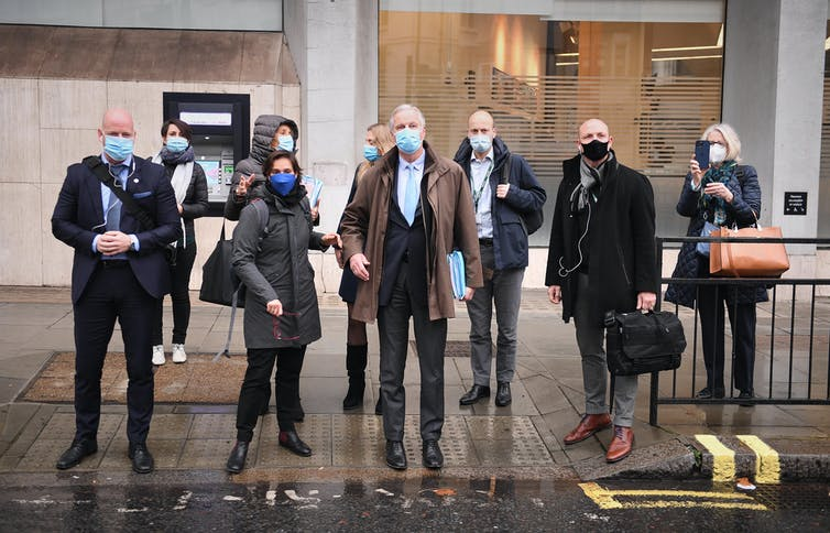 Michel Barnier and his team wearing masks on a London street.
