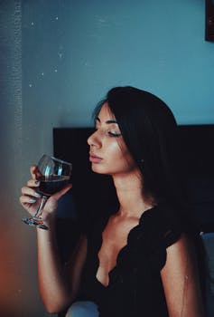 Woman is drinking a glass of red wine.