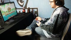 A young man sits in front of a computer with a game console.
