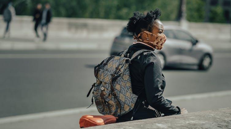 A woman observes her surroundings outside.