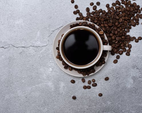 A photo of a cup of coffee sitting among coffee beans.