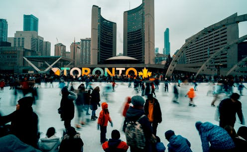 People skate on an outdoor ice rink. City Hall and Toronto sign are in the background.
