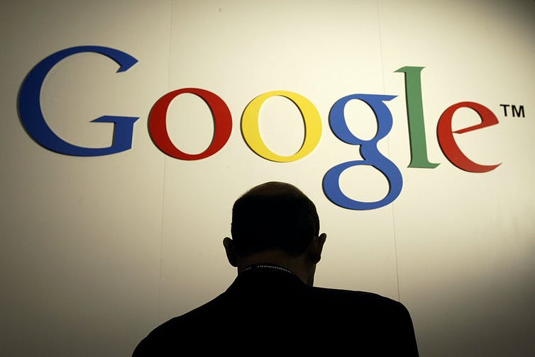 A figure stands under a Google sign.