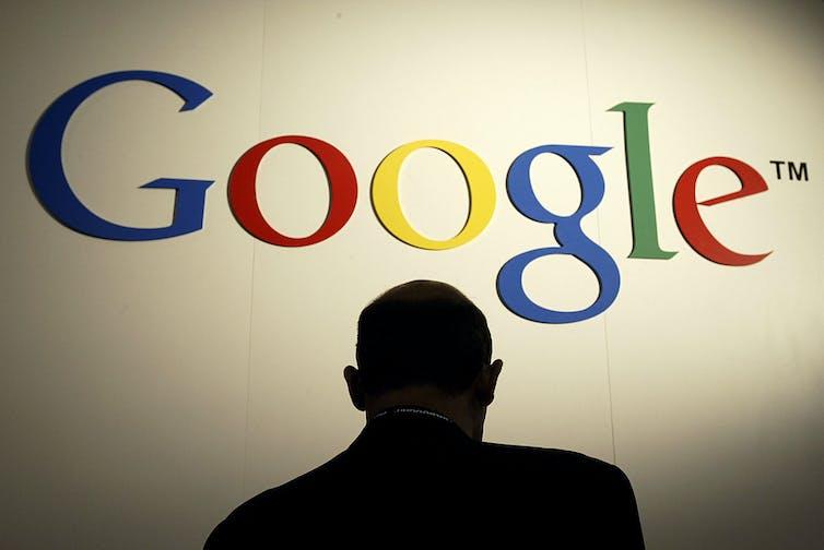 A figure stands under a Google sign.
