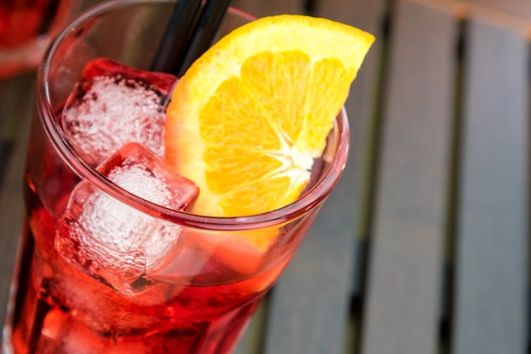 Refreshing red drink in glass with ice cubes and lemon