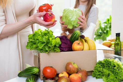 A mother and daughter unpack a box of fruit and vegetables.