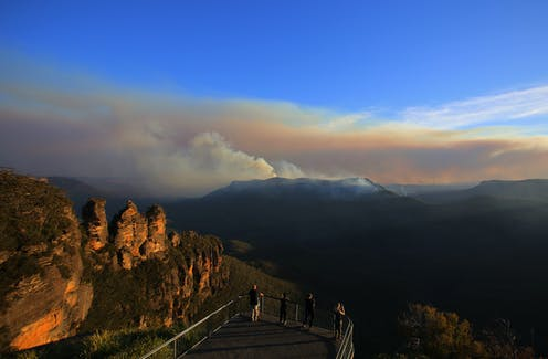 The Three Sisters rock formation is seen as people watch smoke int he distance from the Black Summer fires