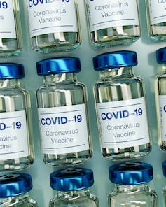 Vials labelled 'COVID-19 Coronavirus Vaccine' lined up in rows.