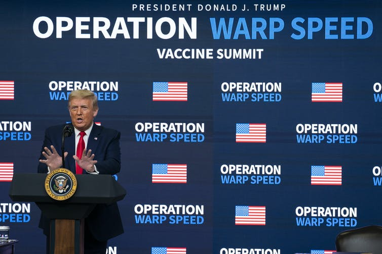 President Donald Trump stands at a podium in front of an Operation Warp Speed banner