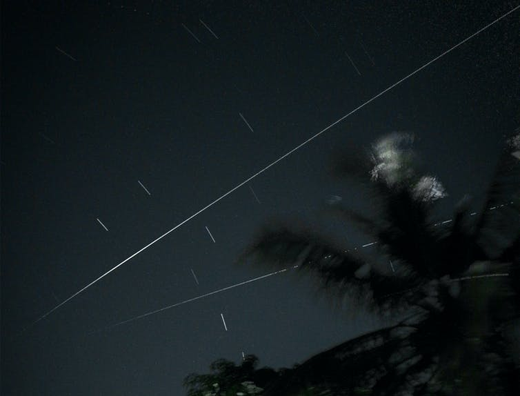 Flash of two meteors across a night sky.