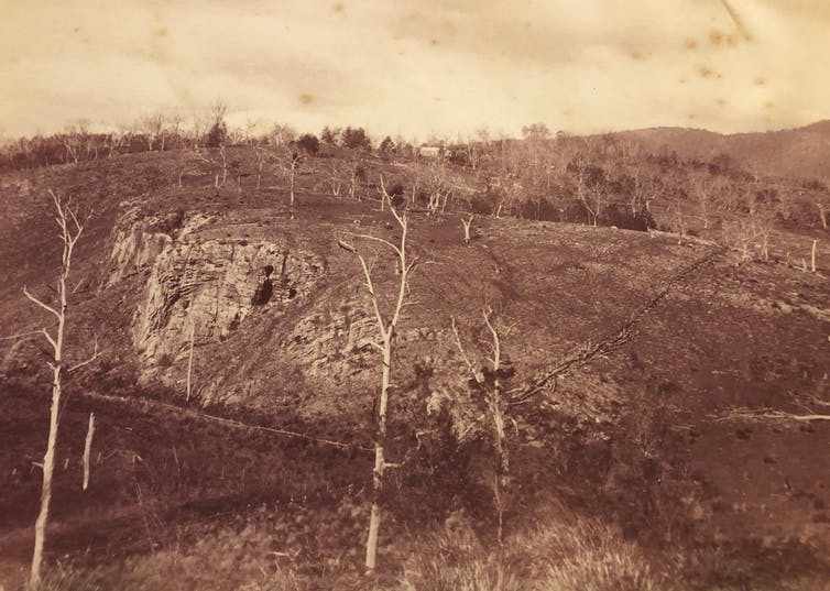 A thinly forested hill with a limestone formation and cave entrance in the middle-distance.