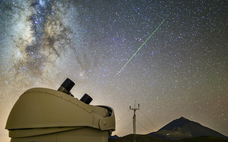 An asteroid streak across the sky with a volcano and telescope in the foreground.