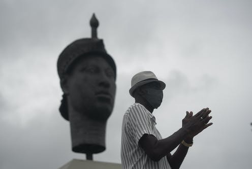 In black and white, the image shows a man in profile in a casual hat, his hands held together in front of him. Behind him is a large statue of a traditional African face.