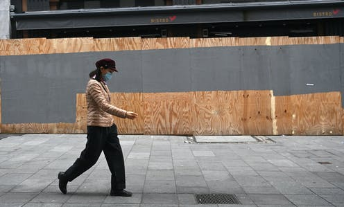 Person wearing a mask walking past a boarded up bistro.