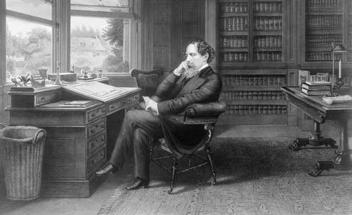 A black and white image of Charles Dickens sitting in his study.