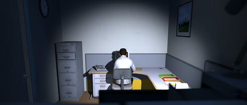 Man sitting in an office cubicle, looking at a computer.