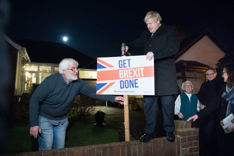 Boris Johnson pictured during the 2019 election campaign hammering a sign reading 'Get Brexit Done' into the ground.