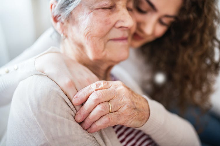 Teenage girl hugging grandmother