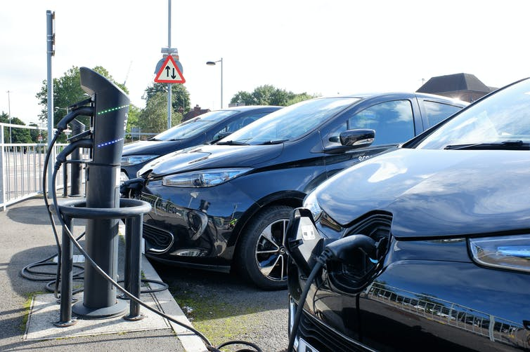 Three electric cars in a line connected to charging points.