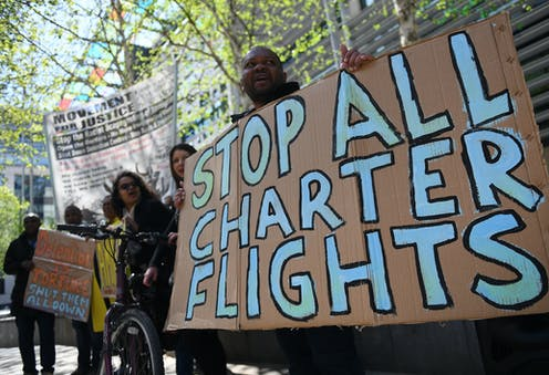 "Man holding sign that says ""stop all charter flights"""